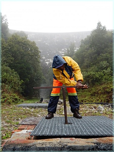 man adjusting outflow at the base of Woodhead Dam